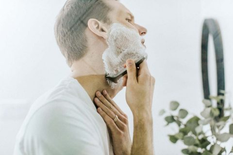 Man using a shaving cream that numbs the skin.